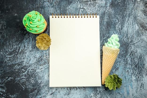 Vista dall'alto gelato albero di natale cupcake ornamenti di natale e un quaderno su superficie grigia