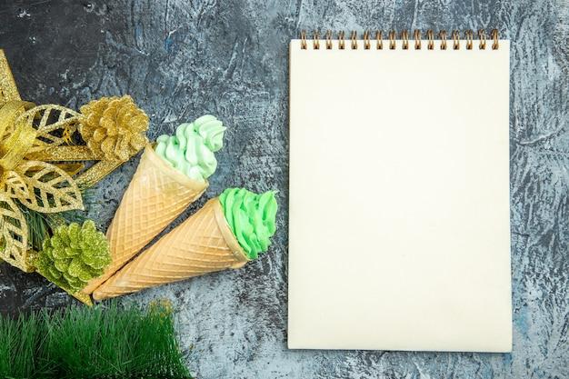 平面図のアイスクリームクリスマスの装飾品と灰色の背景のノートブック