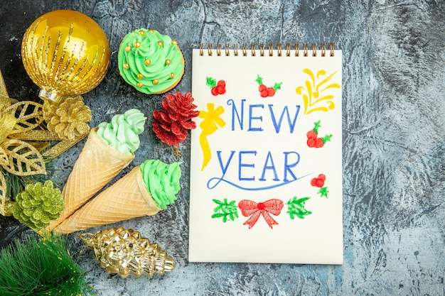 Top view ice creams xmas with new year written on notebook on grey background