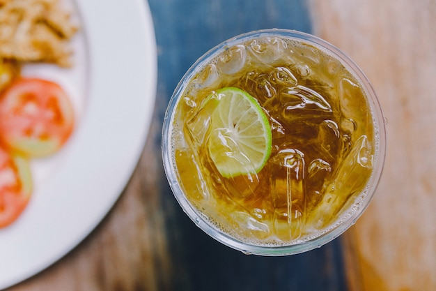 Top view of iced lemon tea in plastic glass on wooden top table.