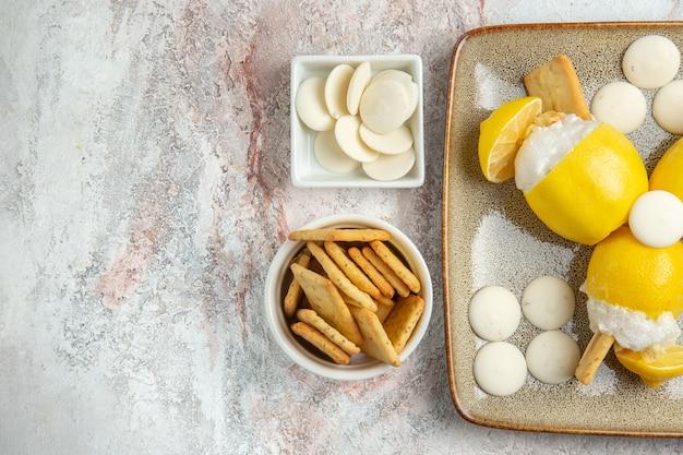 Вид сверху замороженных лимонов с конфетами и печеньем на белом столе