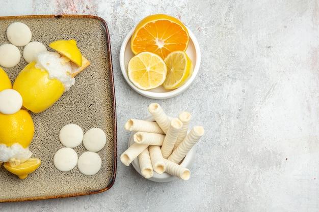 Limoni ghiacciati vista dall'alto con caramelle e biscotti sul tavolo bianco