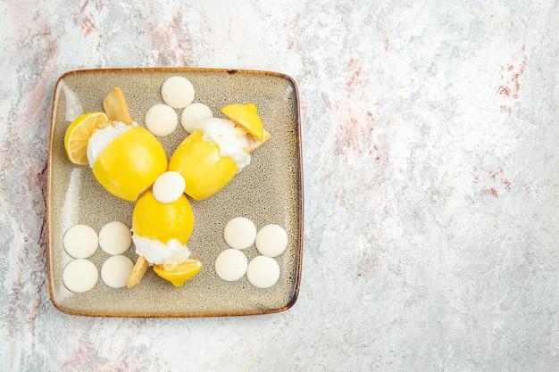 Limoni ghiacciati di vista superiore con le caramelle bianche sul succo del cocktail della bevanda della frutta della tavola bianca