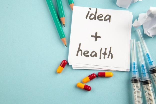 파란색 배경에 알약 주사와 연필로 상위 뷰 아이디어 건강 색상 바이러스 알약 건강 covid lab 유행성 병원 과학