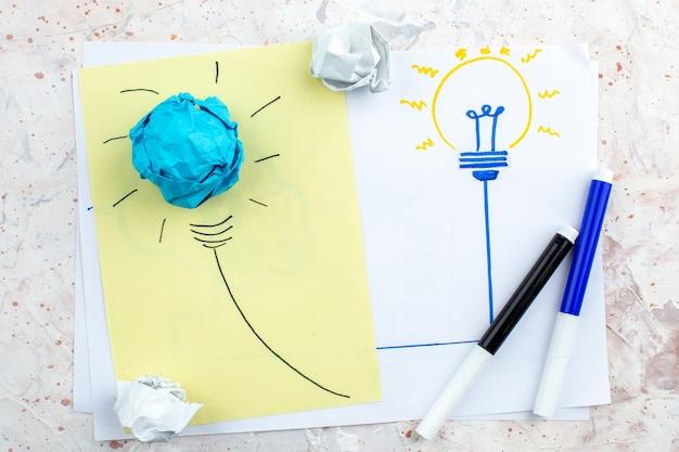 Вид сверху идея лампочка и концепция мозгового штурма рисунок на бумаге черные и синие маркеры на столе