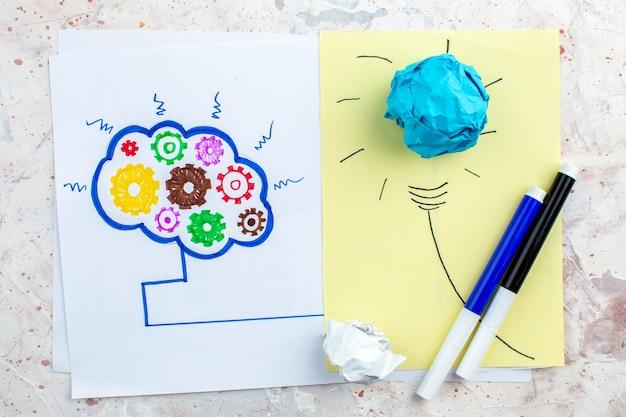 Вид сверху идея лампочка с мятой бумагой черные и синие маркеры концепция мозговой штурм рисунок на бумаге на столе