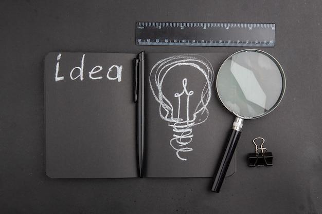Top view idea written on black notebook binder clip lupa ruler pen on dark