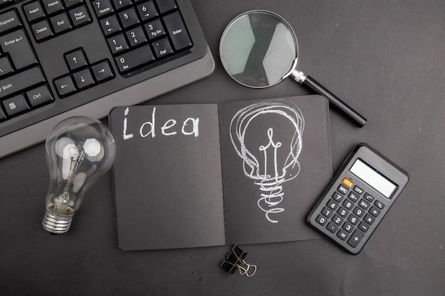 Top view idea written on black notepad keyboard lupa binder clip light bulb calculator on dark