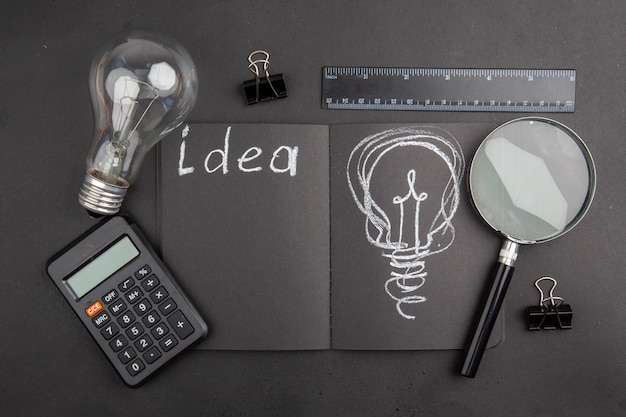 Top view idea written on black notepad light bulb binder clips lupa ruler calculator on dark