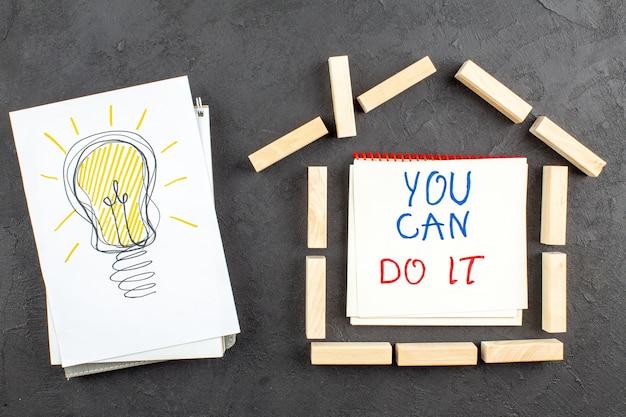 黒のメモ帳に書かれた紙の家の形をした木のブロックに描いた上面図のアイデア電球