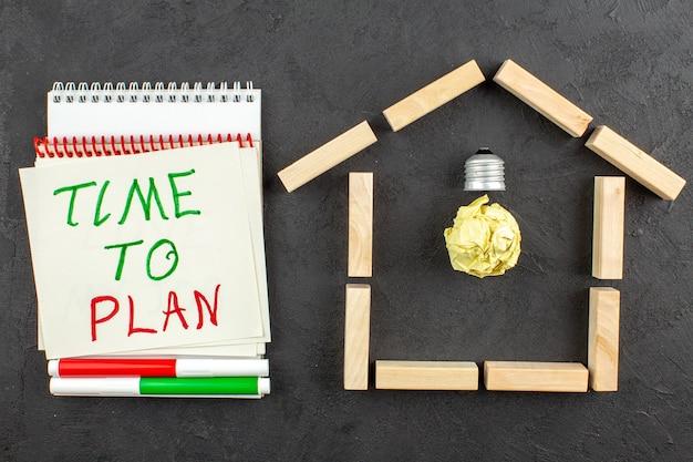 집 모양의 나무 블록에 있는 상단 보기 이상 전구는 메모장 빨간색 및 녹색 마커에 검은색으로 쓰여진 계획 시간을 차단합니다.