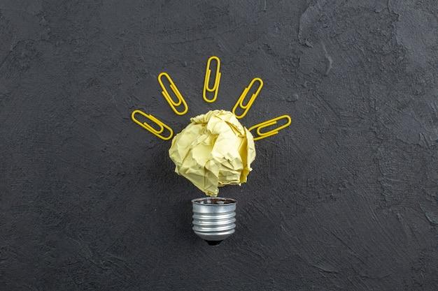 Vista dall'alto idea lampadina fatta da carta e clip di gemme note appiccicose aereo di carta su sfondo scuro