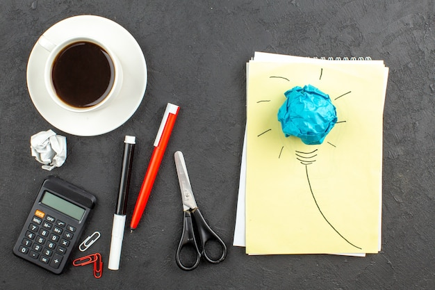 Top view idealight bulb on notepad scissors calculator cup of tea red pen and black marker on black
