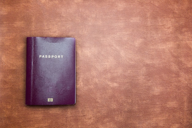 Top view image of blank passport on brown leather wall texture with copy space
