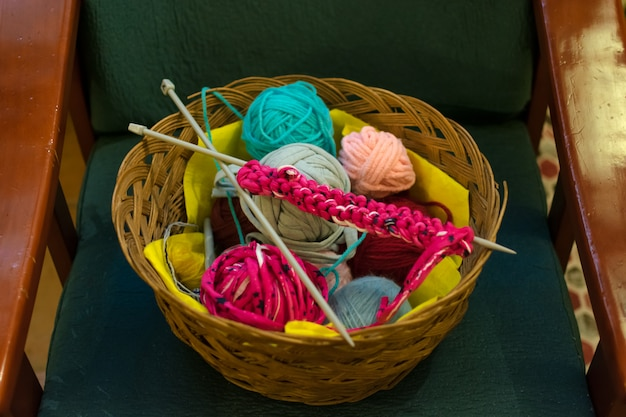 A top view image of crochet yarn and hook on a sofa.