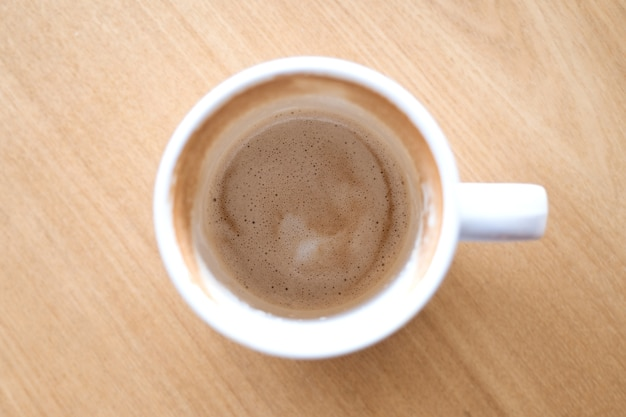 Top view image of finished cup of coffee on wooden table in cafe