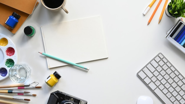 Top view image of graphic designer working table flat lay with painting/drawing equipment, color, paintbrush, pencils, white blank paper, coffee cup, keyboard, keyboard and potted plant on it.
