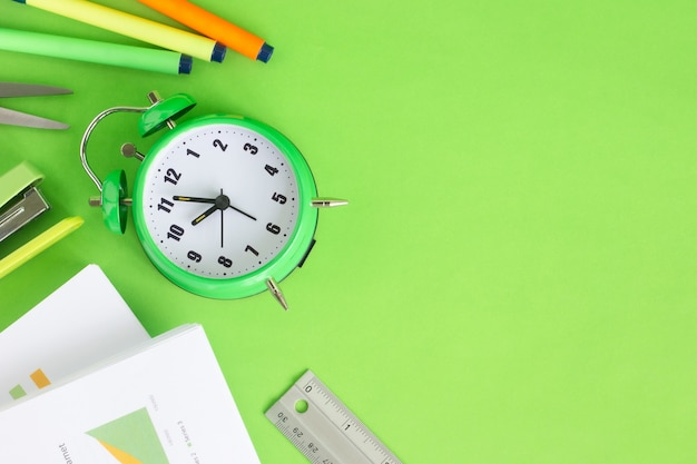 Top view image of green alarm clock with stack of financial documents and work tools on green background