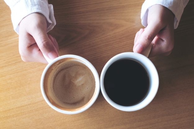 Top view image of hands holding two white cups of coffee on wooden table in cafe