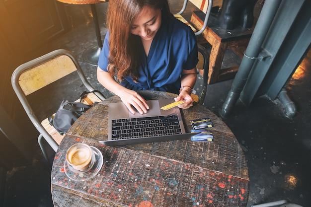 노트북 컴퓨터를 사용하는 동안 신용 카드를 들고 있는 비즈니스 여성의 상위 뷰 이미지