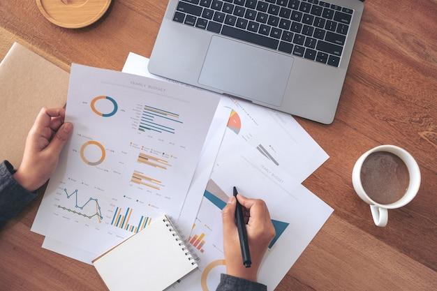 Изображение вида сверху деловой женщины, пишущей и работающей над бизнес-данными и документом с ноутбуком на столе в офисе