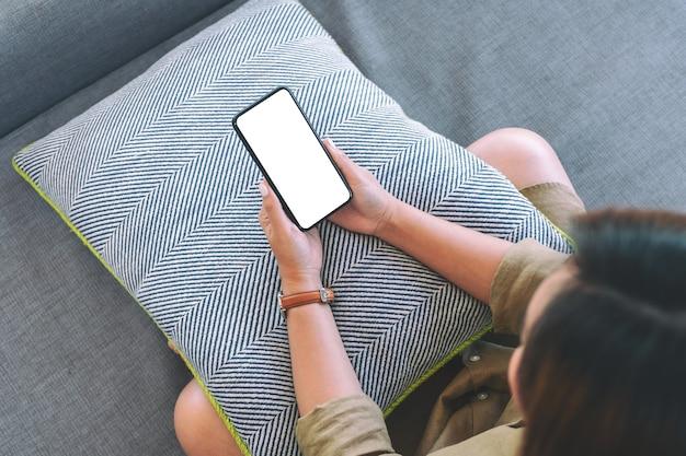 リラックスした気分でリビングルームに座っている間空白の白いデスクトップ画面で黒い携帯電話を保持している女性の上面図画像