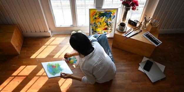 快適なリビングルームの上の絵画のキャンバスの前に座っている間、オイルの色を混ぜているアーティストの女性のトップビューイメージ