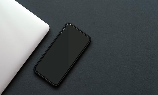 검은 가죽 표면에 검은 화면 스마트 폰 및 노트북 컴퓨터의 상위 뷰 이미지