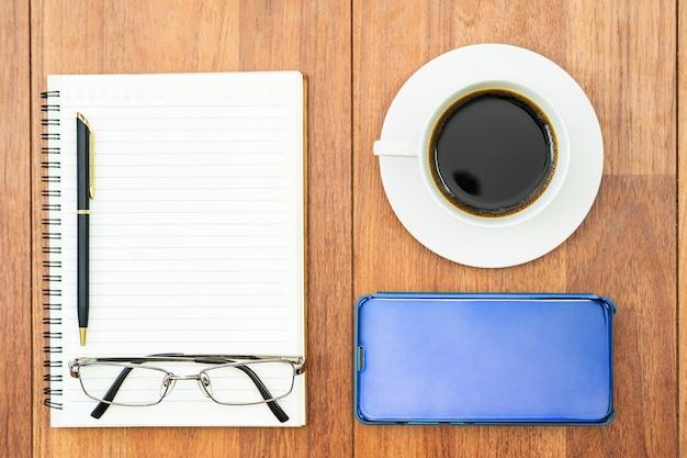 テキストまたはモックアップを追加するための木製のテーブルの背景に目のガラスとコーヒーカップ、ノートブック、携帯電話の上面画像