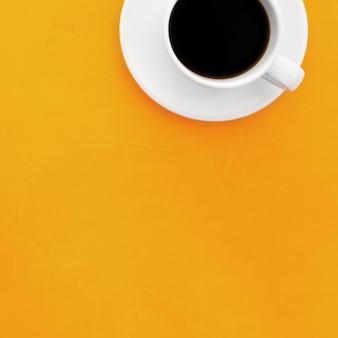 Вид сверху изображение чашки кофе на деревянном желтом фоне