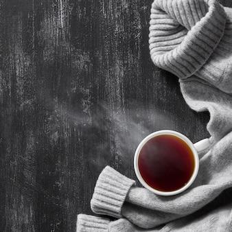 나무 블랙 테이블에 커피 한잔과 함께 회색 아늑한 니트 스웨터의 상위 뷰 이미지