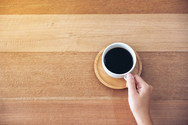 나무 테이블에 마실 뜨거운 커피 한 잔을 들고 손의 상위 뷰 이미지