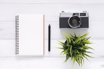 Top view image of open notebook with blank pages and camera on wooden table