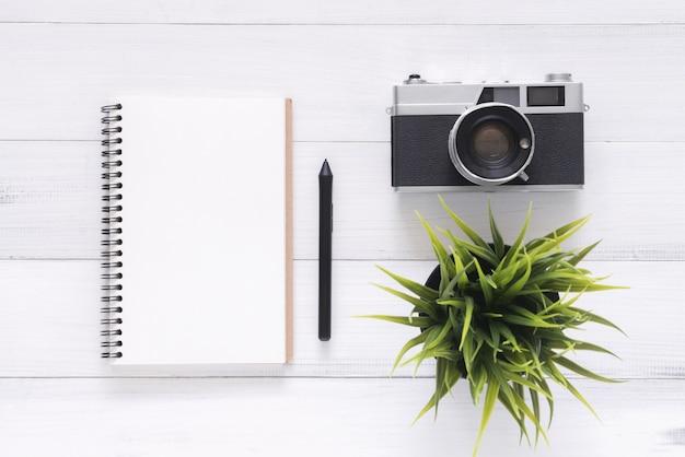 空のページとカメラの木製テーブルで開いているノートブックのトップビュー画像
