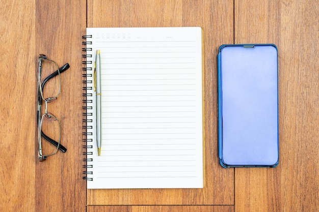 빈 페이지와 핸드폰이있는 열린 노트북의 상위 뷰 이미지, 텍스트 또는 모형을 추가하기위한 나무 테이블 배경에 눈 glasse
