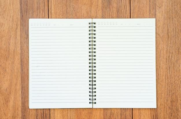 テキストまたはモックアップを追加するための木製のテーブル背景に空白のページを開いているノートブックの上面画像