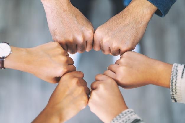 주먹을 쥔 손을 함께 원 안에 넣는 사람들의 상위 뷰 이미지
