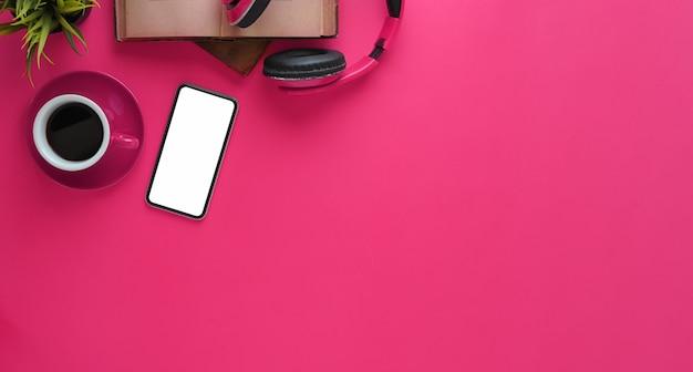 Изображение взгляд сверху розового работая стола. беспроводные наушники, белый пустой экран смартфона, книги, кофейная чашка, растение в горшке вместе на женском столе.