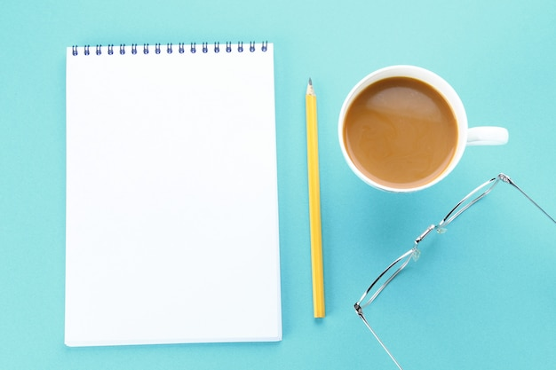 Top view image of open notebook with blank pages and coffee on blue background