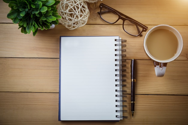 Top view image of open notebook with blank pages and with glasses