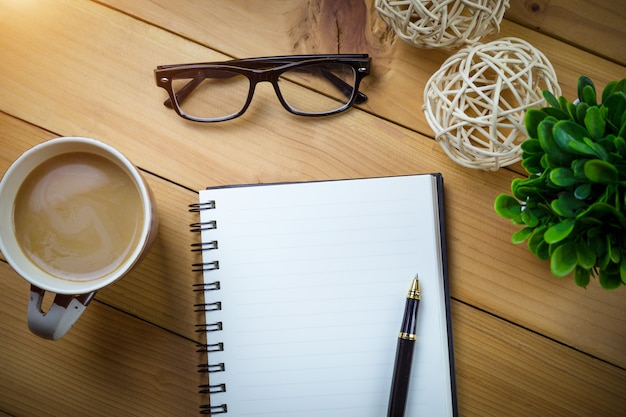 Top view image of open notebook on wooden table.