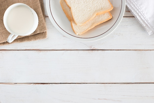 Top view image of sliced bread on dish with hot milk in white cup on white wood table , breakfast in morning, fresh homemade, copy space