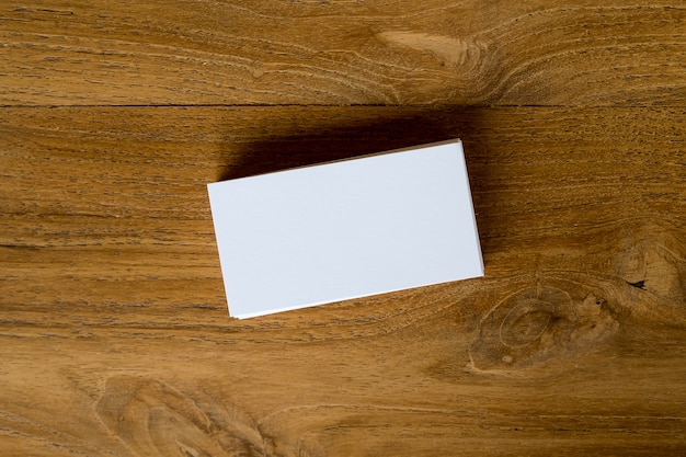 Top view image of stack of business card on wooden table background