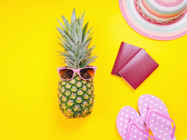 Top view image of  two passports, fresh pineapple wearing sunglasses, beach slippers and hat on a yellow background.