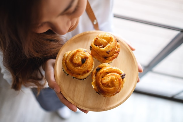 Top view image of a waitress holding and smelling raisin danish in wooden plate