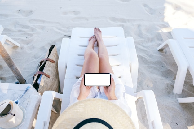 Top view image of a woman holding and using white mobile phone with blank desktop screen while laying down on beach chair