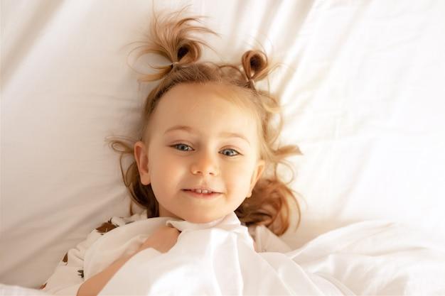 ベッドの平面図快適なマットレス白い毛布寝具嘘子供は広い笑顔を持っていますカメラの子供おはようございます
