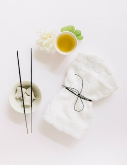 Top view of incense stick; pumice stone; flower; gingko leaf; oil and tied napkin on white background