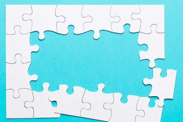 Top view of incomplete puzzle frame over blue backdrop