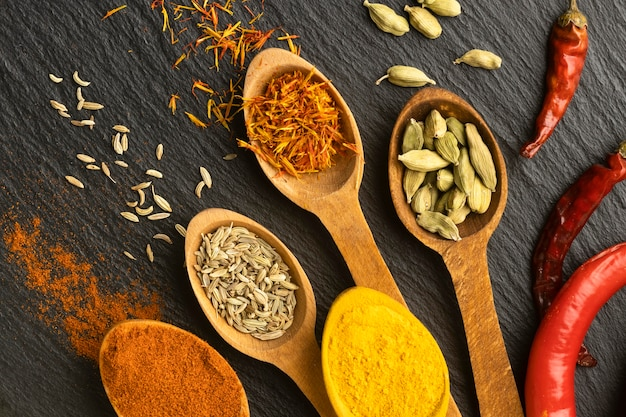 Top view indian spices with wooden spoons